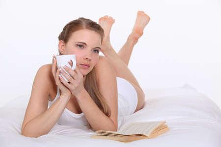 pipe dream: Mujer de tomar caf� en la cama Foto de archivo
