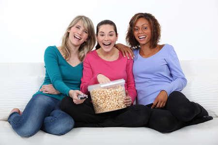 Amigos riendo y comiendo palomitas de maíz