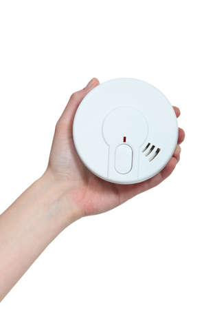 safe and sound: Hand holding a smoke alarm