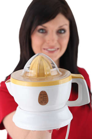 Woman holding electric juicer photo