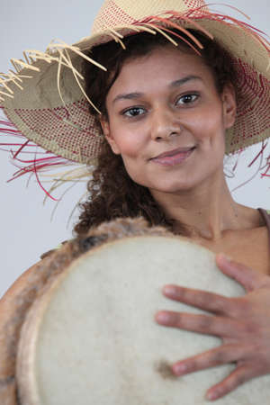 bongo drum: Woman in straw hat holding bongo drum Stock Photo