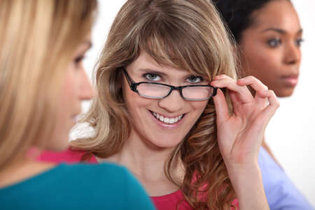 exaltation: Young woman peering over her glasses Stock Photo