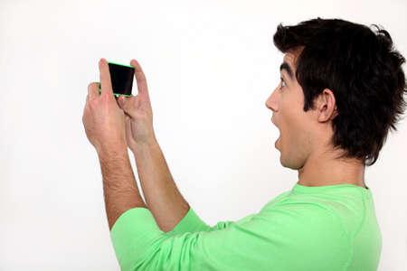 Surprised man watching his cellphone Standard-Bild