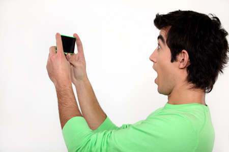 amazed: Surprised man watching his cellphone Stock Photo