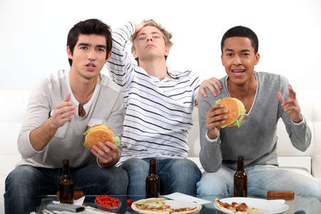 gutted: Lads watching television Stock Photo