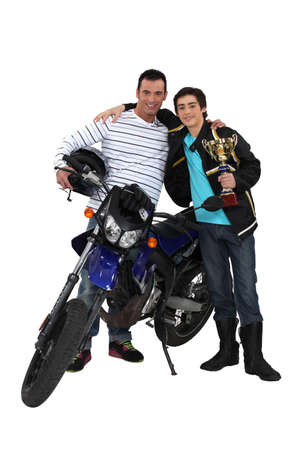 supercross: Father and son with motorcycle and trophy Stock Photo