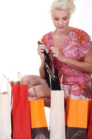 donna in ginocchio: Donna inginocchiata facendo la spesa terzino di lingerie Archivio Fotografico