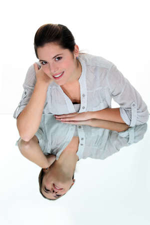 mirrored: Smiling woman leaning on a mirrored surface
