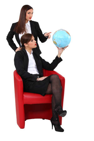 dominate: Two businesswoman looking at a globe