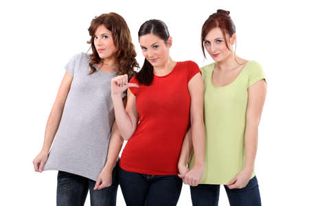 two women showing their t-shirts, one woman pointing finger toward herself photo