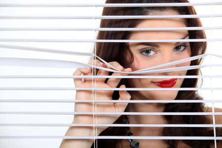 neighbour: pretty woman behind blinds spying upon neighbours