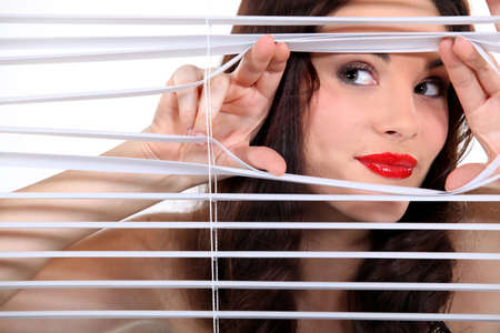 blinds: Woman peering through some blinds