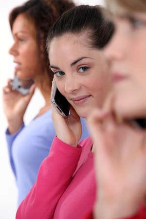 poses de modelos: Tres mujeres que utilizan sus teléfonos móviles Foto de archivo
