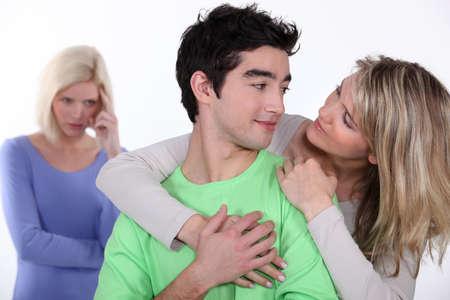 celos: pareja en el amor y la mujer celosa en segundo plano