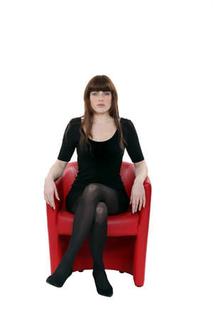 facing: Woman sat on red leather chair Stock Photo