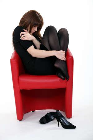 ashamed: La mujer acurrucada en una silla despu�s de un mal d�a Foto de archivo