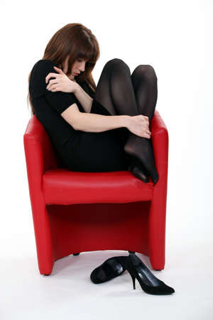 nylons: Woman curled up in a chair after a bad day