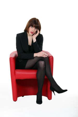 businesswoman suit: Atractiva mujer de negocios sentado en una silla roja