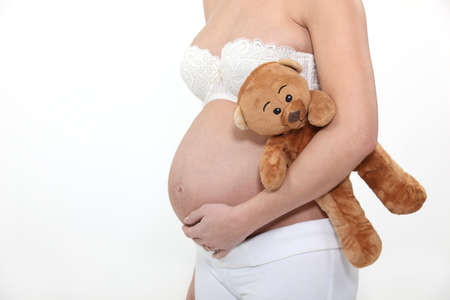 Pregnant woman holding teddy photo
