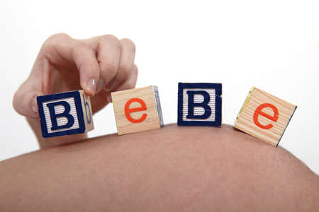 Pregnant woman with building blocks resting on belly photo