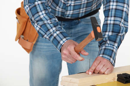 housebuilding: Man hammering nail into wood Stock Photo