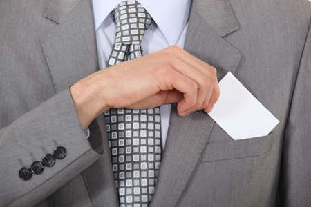 Man putting a business card into his pocket photo