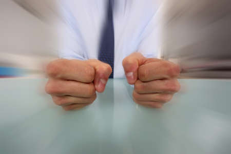 assertive: Businessman banging his fists on his desk