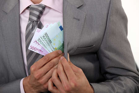 Businessman pulling money out of pocket photo