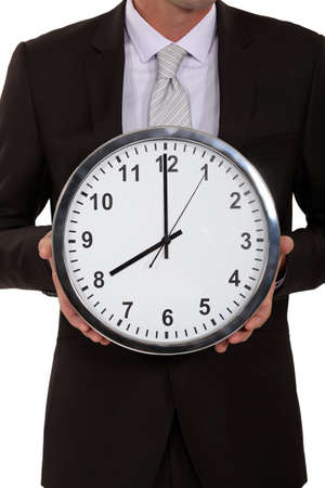 beheaded: A cropped picture of a businessman holding a clock  Stock Photo