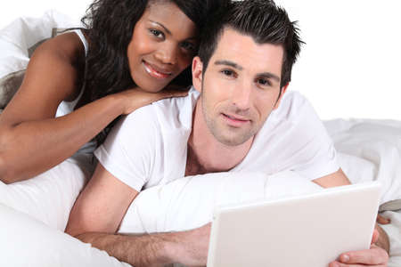 Mixed-race couple using laptop at home photo