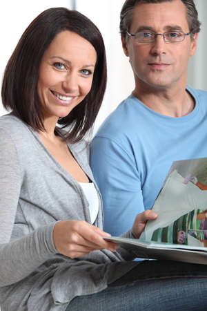 couple at home reading magazines photo