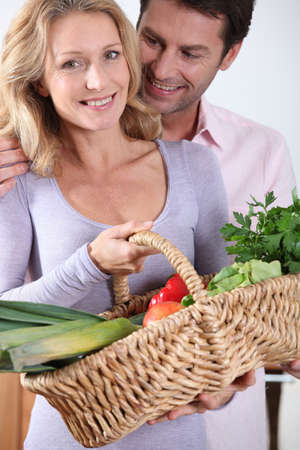 30 40: Husband looking at wife with vegetable basket  Stock Photo