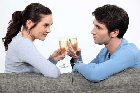 Couple drinking champagne on sofa photo