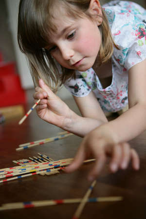 disarray: A little girl playing pick-up sticks