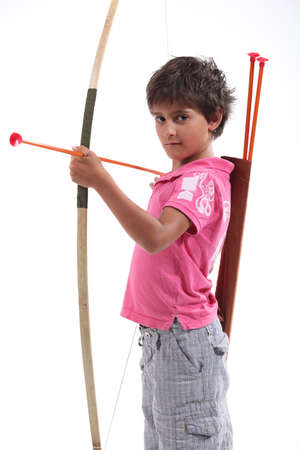 messy hair: A little boy with a bow and arrow  Stock Photo