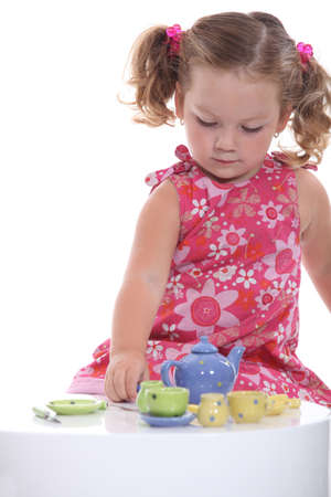 baby cutlery: Little girl playing with model teapot and mugs Stock Photo