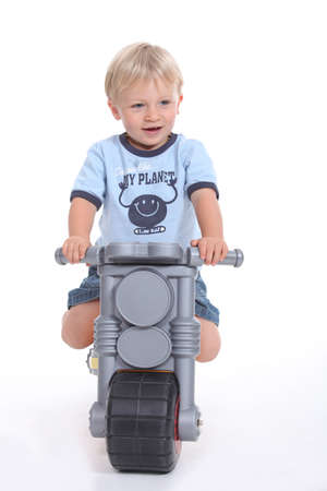 A little boy on his toy motorbike  photo