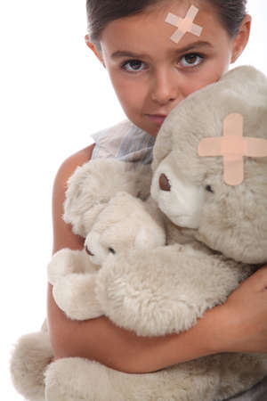 Girl and teddy with a plaster on forehead Stock Photo - 16411565