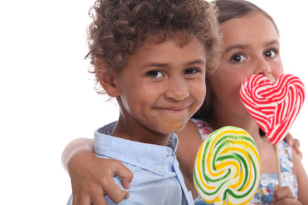 Two young children eating lollipops photo