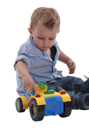12 18 months: Young boy playing with a toy car Stock Photo