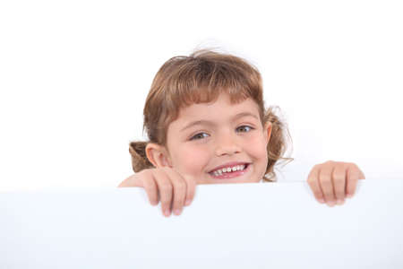 protruding: little blonde girl laughing is half hidden behind a white panel