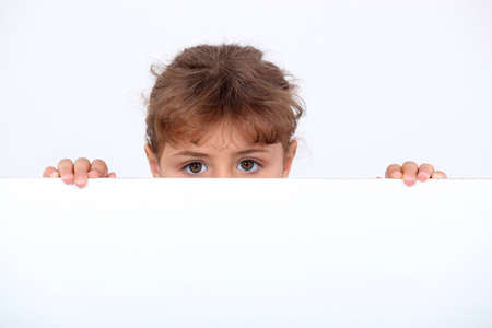 peeking: Girl peeking above a board