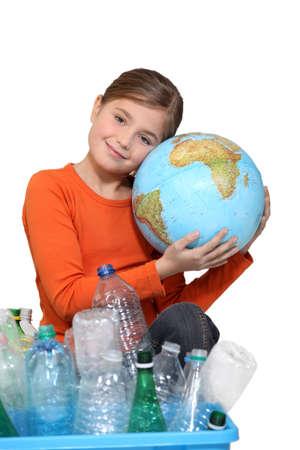 recyclage plastique: Jeune fille �treignant un monde derri�re une bo�te de recyclage du plastique Banque d'images