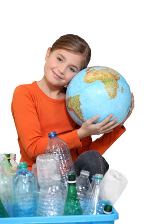 Young girl hugging a globe behind a box of plastic recycling photo