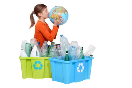 Girl recycling bottles and kissing a globe photo