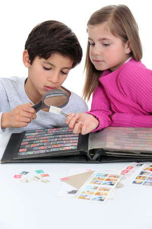 stamp collecting: Two kids collecting stamps  Stock Photo