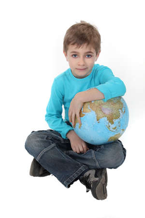 Pale boy with a globe in his lap Stock Photo - 16411340