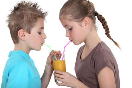 Children sharing a glass of juice photo