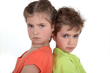 sulk: Brother and sister sulking at each other  Stock Photo