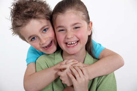 toothy smile: Brother and sister hugging  Stock Photo